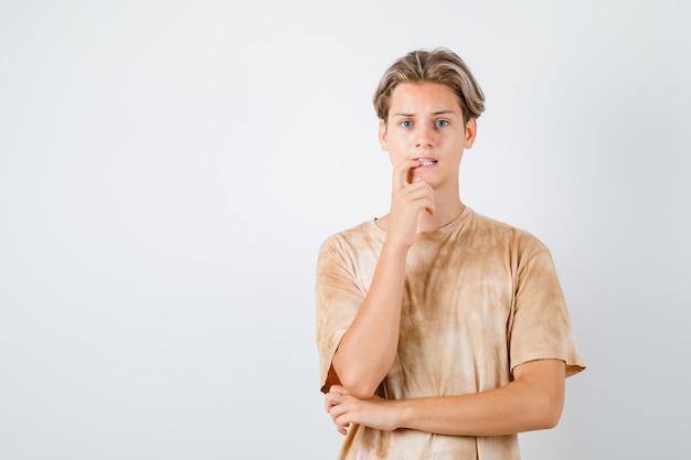 티셔츠를 입은 10대 소년이 손가락을 물고 고민하고 있는 모습, 전면 모습.