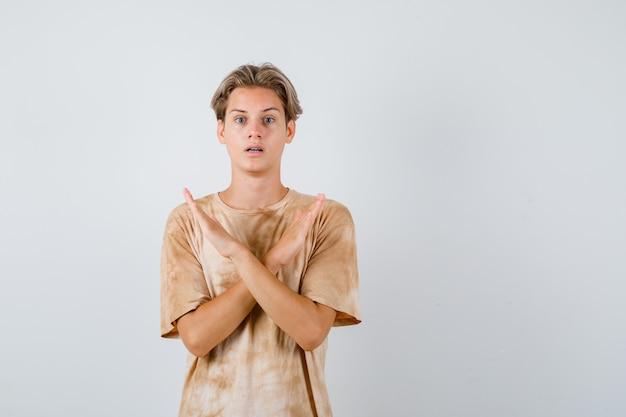 Мальчик-подросток в футболке показывает жест отказа и выглядит встревоженным, вид спереди.