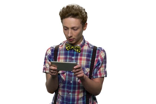 십 대 소년 그의 스마트 폰에서 게임을하고있다. 엔터테인먼트와 현대 기술의 개념. 흰 벽에 고립.