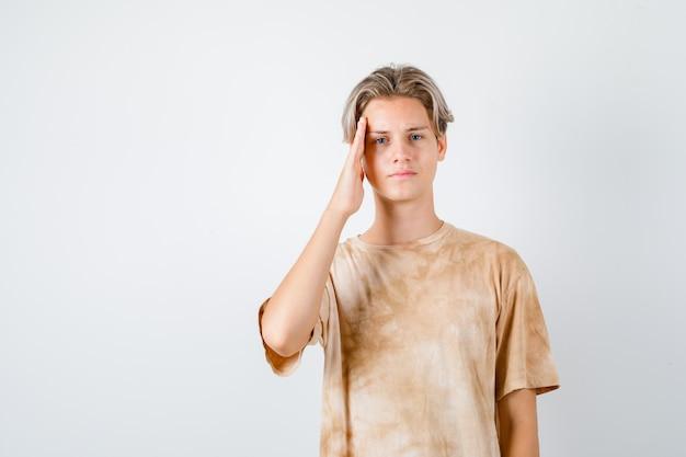 Ragazzo dell'adolescente che tiene la mano sulle tempie in maglietta e sembra triste. vista frontale.