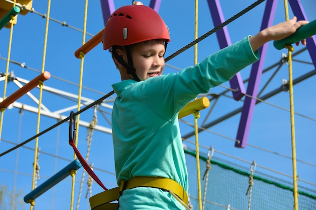 Teenager boy moves the vertical grid on the obstacle course in the amusement park