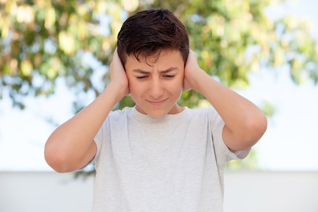 Teenager boy outdoor covering his ears