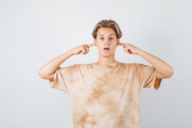 Tシャツに指で耳を差し込んで怖い顔をしている10代の少年、正面図。