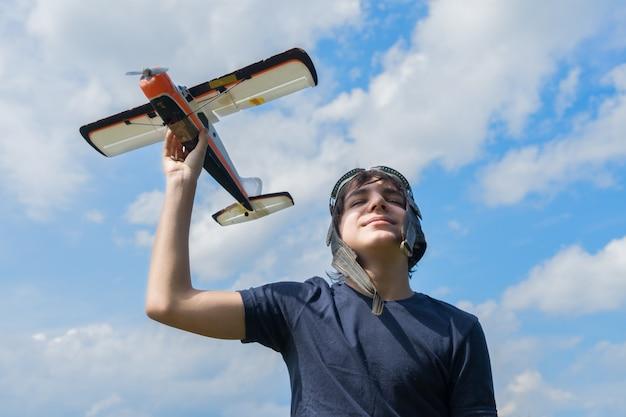 Подросток мальчик ретро пилот playnig с игрушечным самолетом, голубое небо с облаками в фоновом режиме