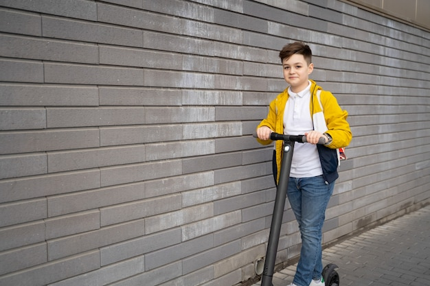 10代の少年が電動スクーターに乗る