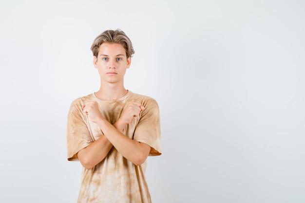 Tシャツで抗議ジェスチャーを示し、真剣に見えるティーンエイジャーの少年。正面図。