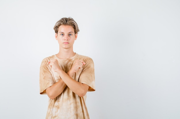 Teenager boy showing protest gesture in t-shirt and looking serious. front view.