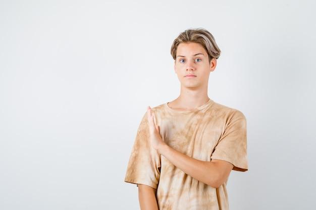 Мальчик-подросток показывает жест остановки в футболке и смотрит осторожно, вид спереди.