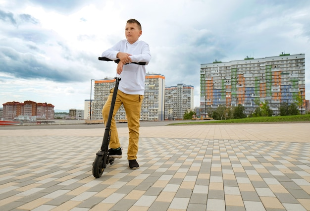 Teenager boy  stand with  electro scooter and looking forward going to ride urban background