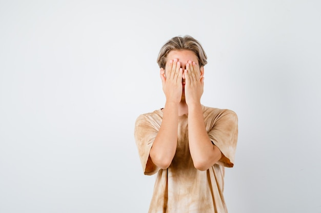 Teenager boy in t-shirt covering face with hands and looking ashamed , front view.