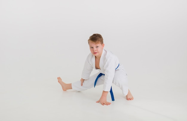Teenager boy in a white kimono with a blue belt does a stretch on a white wall