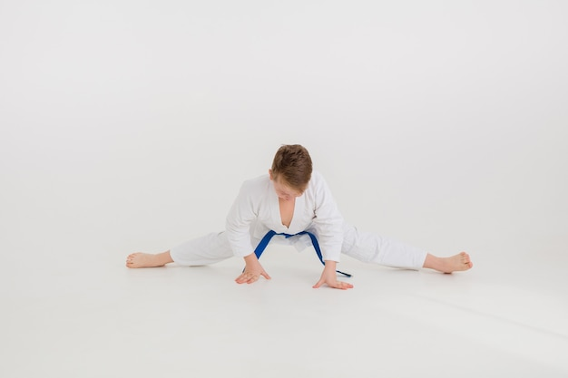 Teenager boy in a white kimono with a blue belt sits on the splits on a white wall