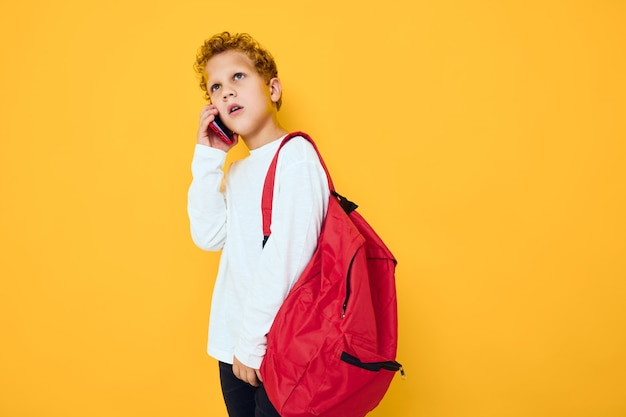 빨간 배낭을 메고 있는 10대 소년이 노란색 배경으로 전화를 건다
