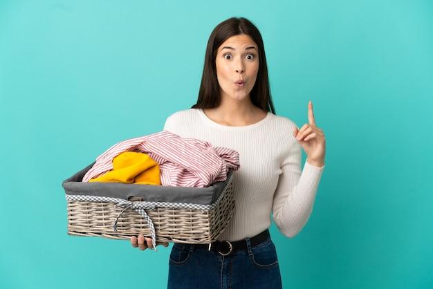 指を持ち上げながら解決策を実現することを意図して青い背景で隔離の服のバスケットを保持している10代のブラジルの女の子
