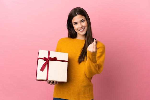 Бразильская девушка-подросток держит подарок на изолированном розовом фоне, делая денежный жест