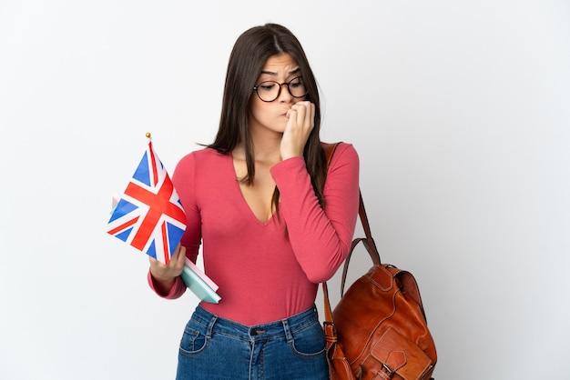 의심을 갖는 흰색 배경에 고립 된 영국 국기를 들고 십 대 브라질 소녀