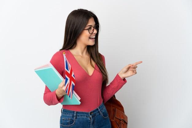 영국 국기를 들고 십 대 브라질 소녀 측면에 손가락을 가리키고 제품을 제시하는 흰색 배경에 고립