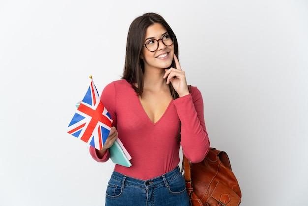 영국 국기를 들고 십 대 브라질 소녀 찾는 동안 아이디어를 생각하는 흰색에 고립