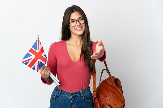Бразильская девушка-подросток держит флаг соединенного королевства на белой стене, пожимая руку для заключения хорошей сделки