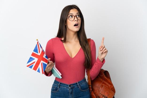 손가락을 가리키는 아이디어를 생각하는 흰 벽에 고립 된 영국 국기를 들고 십 대 브라질 소녀