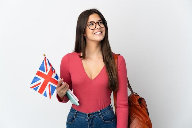 찾는 동안 아이디어를 생각하는 흰 벽에 고립 된 영국 국기를 들고 십 대 브라질 소녀