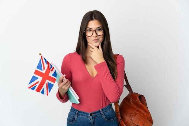 흰 벽에 고립 된 영국 국기를 들고 십 대 브라질 소녀