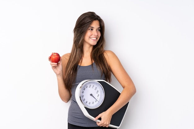 Teenager brazilian girl holding a scale with weighing machine and with an apple