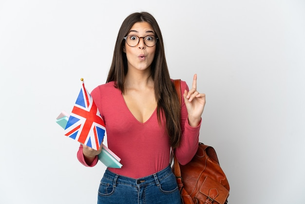 Teenager brazilian girl holding an united kingdom flag isolated on white background intending to realizes the solution while lifting a finger up