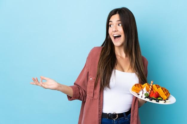 Девушка подростка бразильская держа waffles над изолированной голубой стеной с выражением лица сюрприза