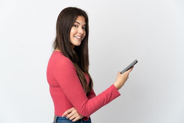 Бразильская девушка-подросток изолирована, держа мобильный телефон и скрестив руки