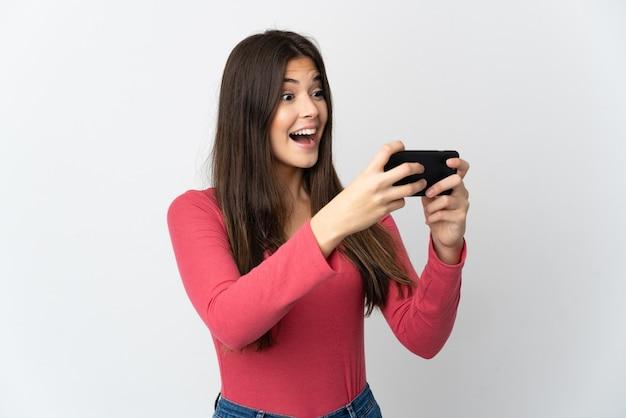 Бразильская девушка подросток, изолированные на белой стене, играя с мобильным телефоном