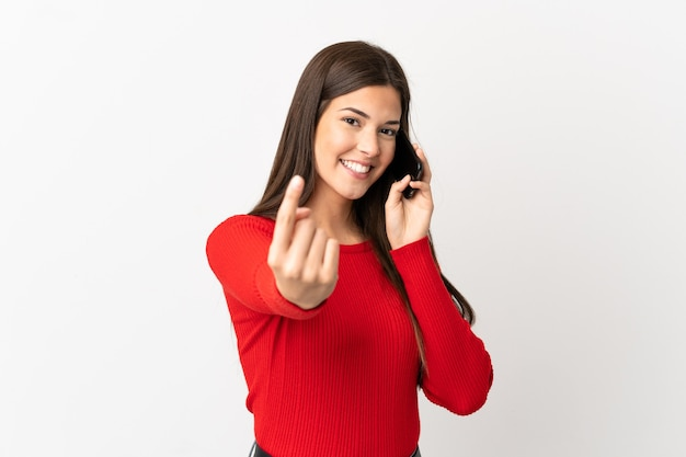 Teenager brazilian girl using mobile phone over isolated white background doing coming gesture