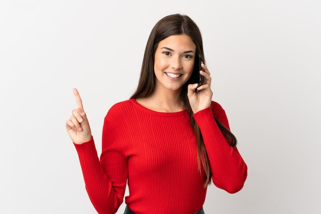 Teenager brazilian girl using mobile phone over isolated white background pointing up a great idea