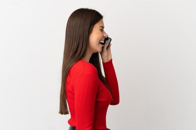 측면 위치에서 웃고 고립 된 흰색 배경 위에 휴대 전화를 사용하는 십 대 브라질 소녀