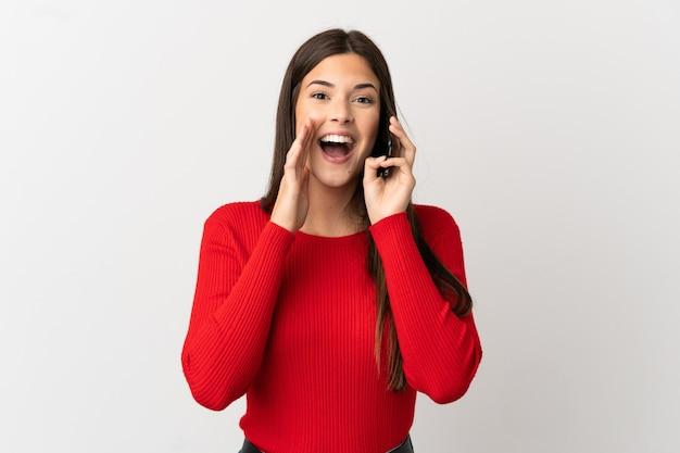 孤立した白い背景の上に携帯電話を使用して、口を大きく開いて叫んでいる 10 代のブラジルの女の子