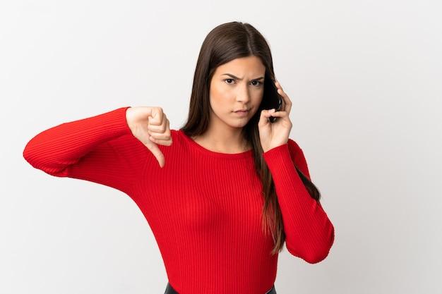 Бразильская девушка-подросток, использующая мобильный телефон на изолированном белом фоне, показывает большой палец вниз с отрицательным выражением лица