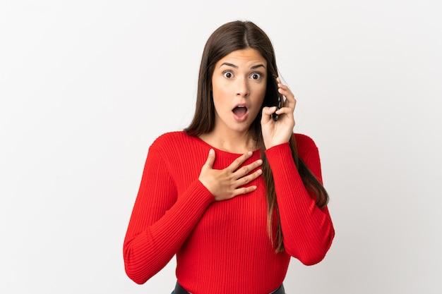 Бразильская девушка-подросток, использующая мобильный телефон на изолированном белом фоне, удивлена и шокирована, глядя вправо