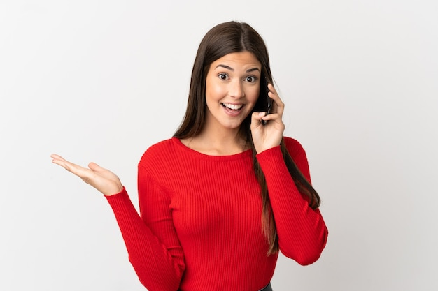 Бразильская девушка-подросток с помощью мобильного телефона на изолированном белом фоне с шокированным выражением лица