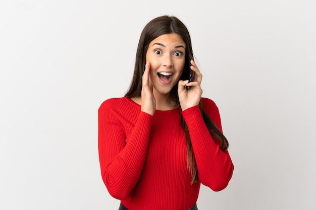 Бразильская девушка-подросток, использующая мобильный телефон на изолированном белом фоне с удивлением и шокированным выражением лица