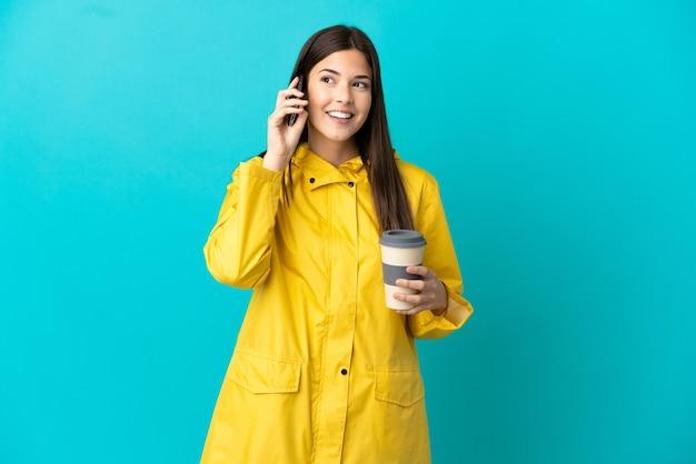 孤立した青い背景に防雨コートを着た 10 代のブラジルの女の子がコーヒーと携帯電話を持ち去る