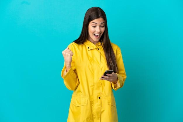 孤立した青い背景の上に防雨コートを着て驚いてメッセージを送信する10代のブラジルの女の子