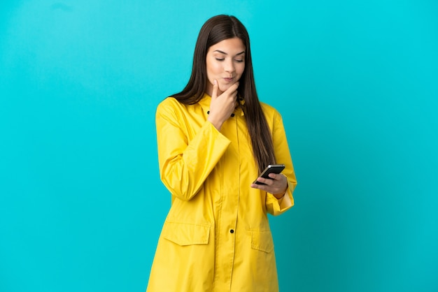 孤立した青い背景に防雨コートを着た 10 代のブラジル人の女の子が考え、メッセージを送る