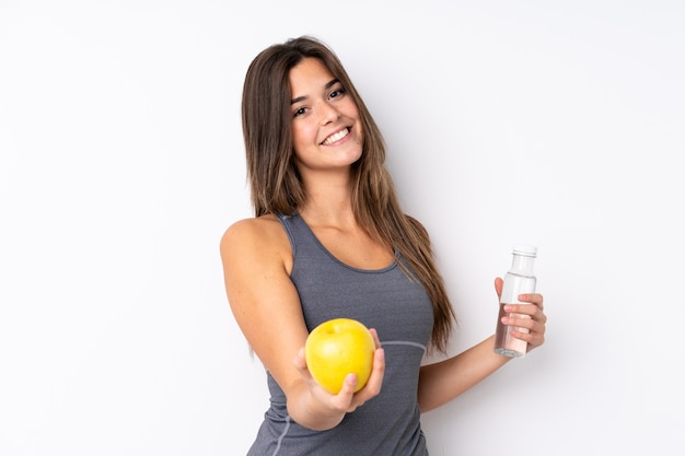 Teenager brazilian girl with an apple and a with a bottle of water