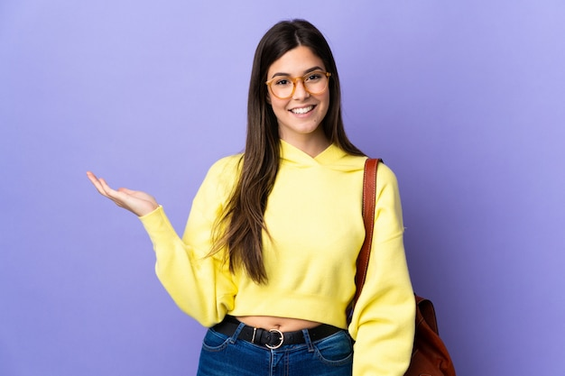Teenager brazilian student girl over isolated purple wall holding copyspace imaginary on the palm