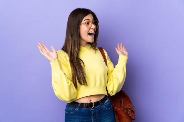 Девушка студента подростка бразильская над изолированной фиолетовой стеной с выражением лица сюрприза