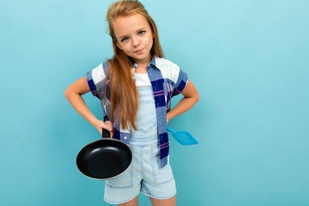 Кавказская девушка подростка собирается пожарить что-то с кастрюлей на синем фоне