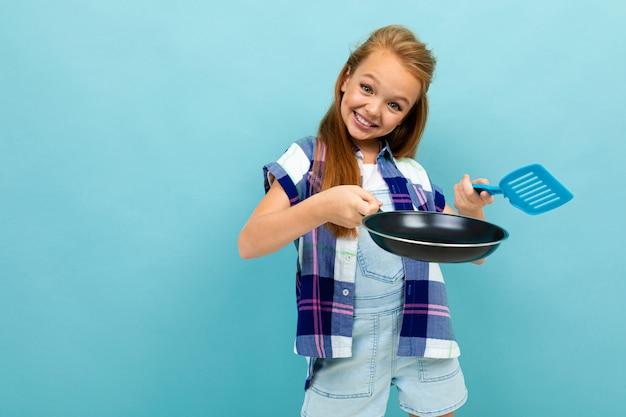 Кавказская девушка подростка собирается жарить что-то с кастрюлей, изолированных на синем