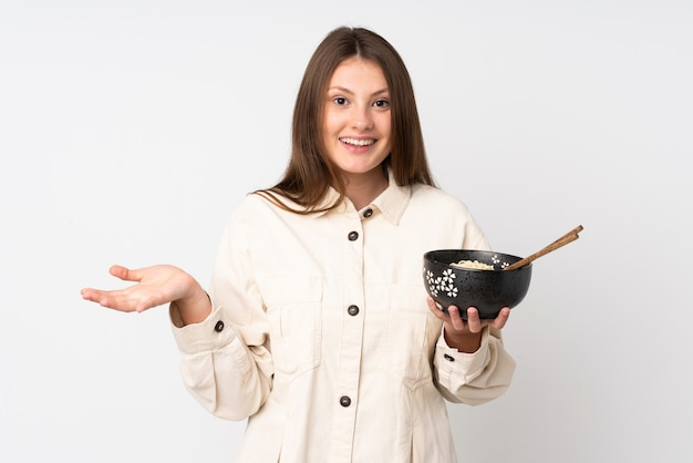 箸で麺のボウルを押しながらショックを受けた表情で白い壁に分離された10代の白人少女