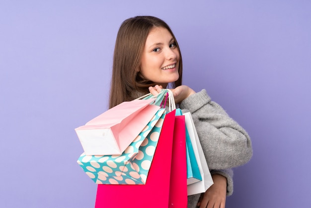 Teenager caucasian girl isolated on purple holding shopping bags and smiling