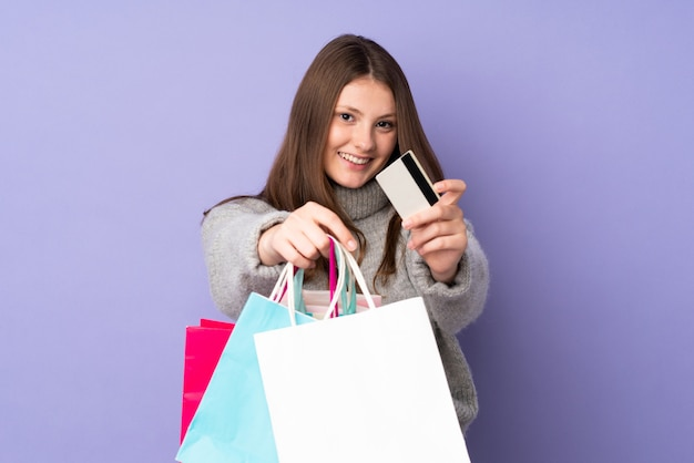 Teenager caucasian girl isolated on purple wall holding shopping bags and a credit card